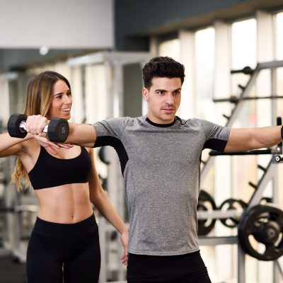 Female personal trainer helping a young man lift dumbells while working out in a gym